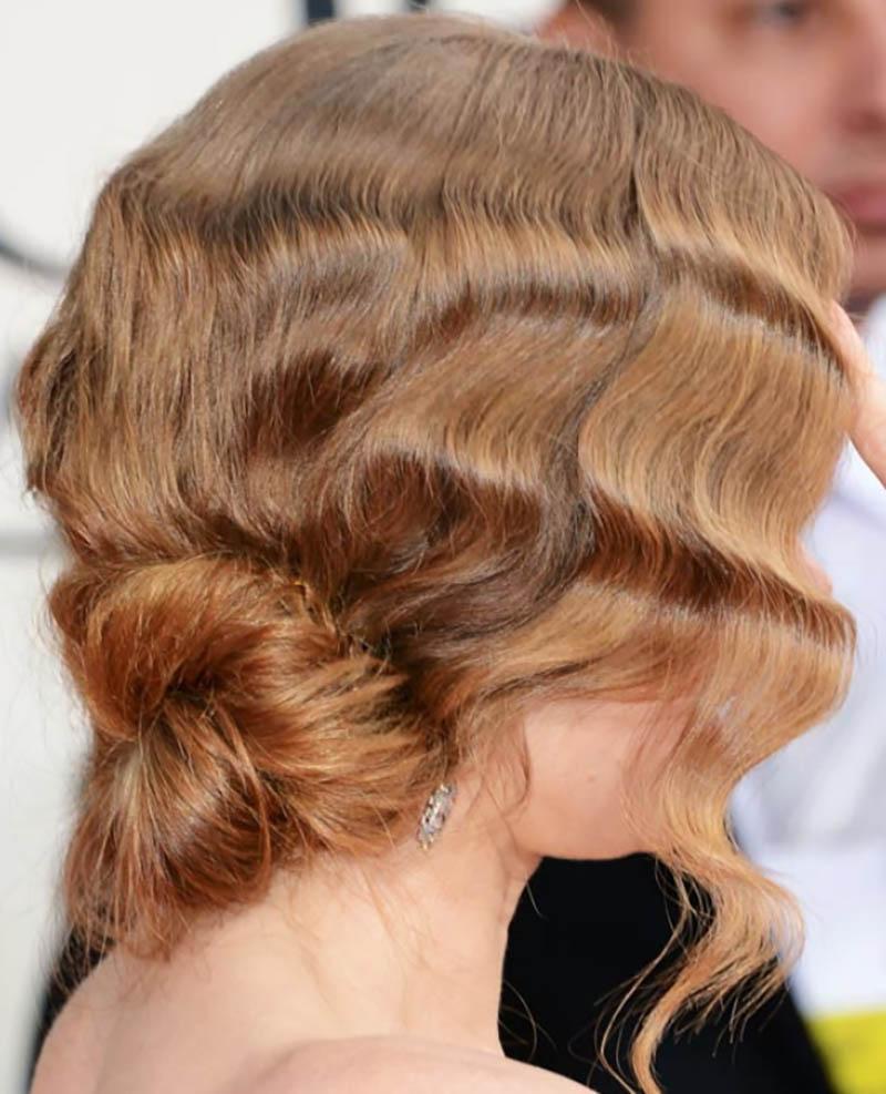 Búi tóc xoăn thấp lộn xộn với kết cấu phía trên và tóc mái lệch