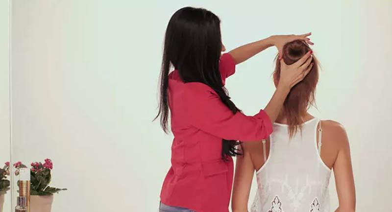 Sau đó dùng tóc luồn lần lượt qua để che chiếc bánh donut xốp đó lại, bạn sẽ phải dùng tay để giữ chặt tóc.